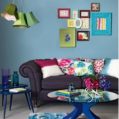 A vibrant blue-flocked coffee table gives this traditional living room a bright new twist. The collage of framed prints, clustered light shades and patchwork cushions add to the quirky, eclectic feel.