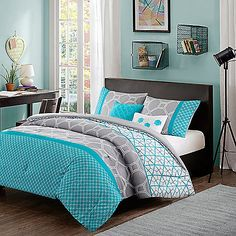 Add a modern look to your bedroom with the bright Clara Reversible Comforter Set. The lively bedding features a hexagon design on a grey ground with a geometric design on a bright aqua ground bottom.