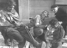 Medic tends to wounded German PoW.  A medic from the 45th Medical Bn tends to wounded German prisoners at Frameries, Belgium, on 9/2/44. At top right is an assisting Belgium civilian.(rudeerude)