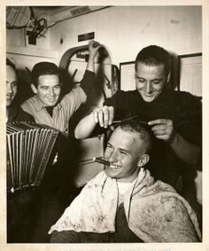 US sailors  It is GI haircut—very GI—as Coast Guardsman Nolan Etchison, Torpedoman Third Class, of Lockport Illinois (seated) goes to the barber shop aboard a Coast Guard destroyer escort somewhere in the Atlantic. Happily he chews a cigar while Harold Mason, a Signalman Second Class, of Rhinelander, Wisconsin gives him a clipping.  Next in line is Henry O' Connor, Seaman First Class, of Pittsfield Massachusetts.