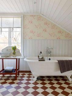 Badrummet har viktorianska klinkerplattor och pärlspont målad med ljusgrå linoljefärg. Tapet, Colefax & Fowler.
