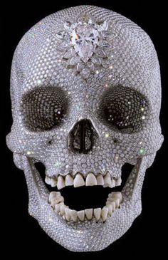 """Damien Hirst's sculpture, """"For The Love of God"""". A platinum skull encrusted with 8,601 diamonds, eye and nose sockets filled with hundreds of jewels and a 52-carat pear-shaped stone fixed on the forehead, bordered with 14 diamonds. It was influenced by Mexican skulls encrusted in turquoise. The skull has been sold to an investment group for $100 million. What's not to love?"""