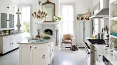 Designer Annie Brahler upgraded a vintage demilune chest by adding rear cabinets and a marble top to create the central island in the kitchen of her Jacksonville, Illinois, Victorian. Stainless-stell range and hood by Thermador.   - HouseBeautiful.com