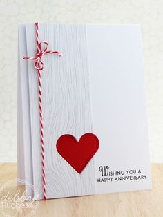 handmade anniversary card ... Clean & Simple by kimberly ... wide top to bottom panel stamped wood grain in pale gray .. negative space die cut heart with a bright red heart on the baste card ... some red and white baker's twine and a sentiment ... not too difficult ... luv the simplicity of the message ...