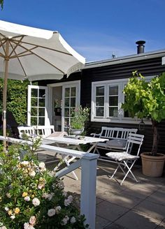 Relaxing summer house patio with simple white wood furniture. Cottage Plan, Cozy Cottage, Black House Exterior, Interior And Exterior, Outdoor Rooms, Outdoor Living, Summer House Interiors, Pintura Exterior, Simple House