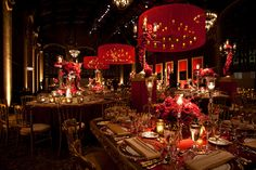 A bounty of red and merlot roses set beneath custom wrought iron chandeliers with sheer drum shades housing pillar candles. Extravagant Wedding Decor, Glamour Decor, Wrought Iron Chandeliers, Event Lighting, Branding, Elegant, Event Design, Pillar Candles, Wedding Styles