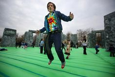 "Jeremy Deller bounces on his new work ""Sacrilege,"" a full-scale inflatable replica of Stonehenge and part of the Glasgow International Festival of Visual Arts. (Photo by Jeff J. Mitchell/Getty Images.)"