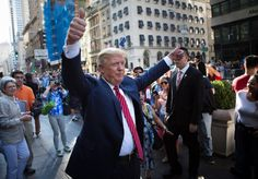 Republican Presidential candidate Donald Trump gestures to the crowd gathered in front of the Trump Tower ahead of the passing of the Pope's motorcade in New York