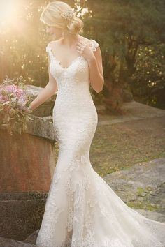 Embrace your femininity and highlight your beautiful shoulders in this stunning lace over satin bridal gown from the Essense of Australia wedding dress collection. It features an illusion tattoo lace design, scalloped hem, and a gorgeous train. The back zips up under fabric buttons.