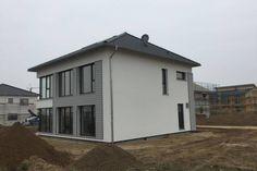 Entstehung Passivhaus/Fertighaus mit Holzverkleidung in Hellgrau.