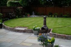 large circular lawn with curved pathway surrounding and tall log burner