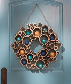 "Made from ""slices"" of pipes! I think one could also use kitchen paper card rolls, and instead of a wreath a pine tree could be formed."