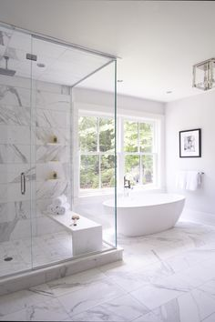 Love The Shower Bench An Oval Freestanding Bathtub Paired With A Modern  Polished Nickel Tub Filler Is Positioned On White Marble Floor Tiles  Beneath A ...