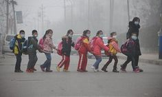 Students in face masks walk across the street in Jinan, in east China's Shandong province