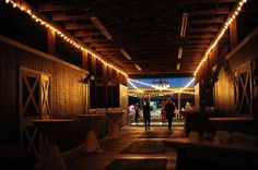 A rustic barn gets an elegant touch with twinkly lights and white tablecloths for a wedding reception. #countrywedding http://www.gactv.com/gac/photos/article/0,3524,GAC_42725_6075192_01,00.html?soc=pinterest