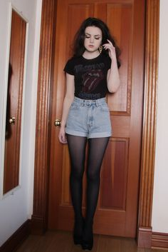 black band tee and high waist cuffed denim shorts worn with sheer black tights