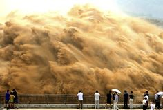 Visitors watch water gushing from the Xiaolangdi Reservoir on the Yellow River during a sand-washing operation.