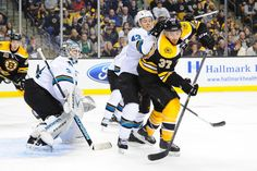 San Jose Sharks forward John McCarthy battles for positioning against Boston Bruins forward Patrice Bergeron in front of Sharks goaltender Antti Niemi (Oct. 24, 2013).