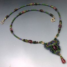 I mixed 4 colors of thread on a hammered wire to form this neckpiece- light and dark green, purple and khaki green are the background for a center oval bead of deep clear purple glass lined by metallic luster green beads. I also used metallic purple, opaque rainbow luster