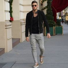 Busy days call for a simple yet stylish outfit, such as a black suede bomber and grey chinos. Why not add camel leopard low top sneakers to the mix for a more relaxed feel? Shop this look on Lookastic: https://lookastic.com/men/looks/bomber-jacket-tank-chinos/20184 — Black Tank — Black Suede Bomber Jacket — Black Sunglasses — Grey Chinos — Tan Leopard Low Top Sneakers