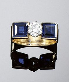 SAPPHIRE AND DIAMOND RING, CARTIER, 1930S. Claw set to the centre with a circular-cut diamond set between step-cut sapphire shoulders, size L, rubbed Cartier signature, signed Made in France, numbered, French assay marks.
