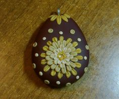 Teardrop shaped polymer clay pendant, handmade with applique technique, one of a kind. Burgundy, with a flower, leaves and dots in various shades of gold, with yellow Swarovski crystal. By Lis Shteindel