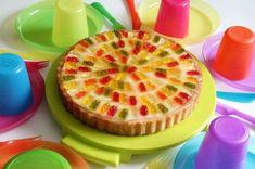 Für die Gummibärchen-Torte den Obstboden auf eine Servierplatte setzen und mit der Marmelade bestreichen. Dann aus dem Vanillepuddingpulver, dem Zucker und der Milch nach Packungsanleitung einen Vanillepudding kochen. Diesen anschließend auf den Tortenboden geben und gleichmäßig verteilen.