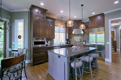 Mixing traditional and contemporary elements, featuring stained cabinets with a…