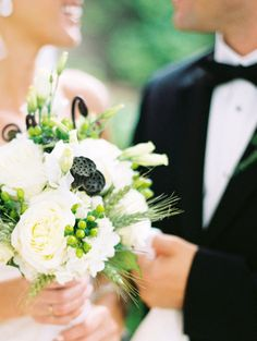 green and white bridal bouquet with roses and dried lotus pods