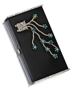 An Art Deco 18 karat gold, platinum and black enamel gem-set compact, Van Cleef & Arpels, Paris, circa 1925. The rectangular hinged case applied all over with black enamel, the lid decorated in Chinese taste with a flowering tree set with small round turquoise and ruby cabochons and single-cut, baguette and fancy-shaped diamonds, the sides bordered in baguette diamonds, the interior with fitted mirror and powder compartment, signed Van Cleef & Arpels, Paris, numbered. #VanCleef #Arpels…
