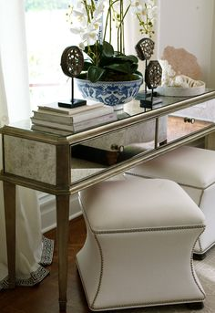 antiqued mirror console table + upholstered nailhead stools + vignette