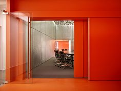 Remodel of ImageNet Carrollton by Elliott + Associates Architects. 30' wide sliding doors separate the training room and café. Suspended recycled toner cartridges create a celestial ceiling in the training room and aluminum bubble wrap provides a glistening wall surface. The cafe showcases the new corporate color - oven-hot orange.  Photography by Scott McDonald/Gray City Studios