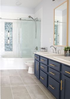 DIY bathroom renovation! Modern classic bathroom design with navy blue vanity, subway tile shower, large shower niche, and textured gray floor tile. Transitional design.