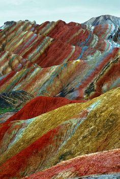 Relevo de Danxia, China As cores são reais e fazem parte de um fenômeno geológico singular que é o resultado de uma acumulação de milhões de anos de arenito de cor vermelha e outras rochas, em grande parte do Cretáceo, que formam desenhos fantásticos que lembram ondas do mar.