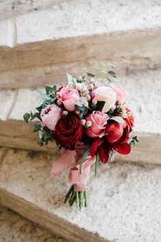 Lovely red's and pink's in this posy wedding bouquet. A posy bouquet is typically small and round so it can be held easily in one hand. It can either be constructed loosely with a hand-wrapped, color-coordinated ribbon and an embellished trim, or by replacing the stems with florists wire for a more structured look with one type of flower.