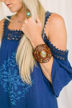 Make a gorgeous statement in our bohemian handmade leather cuff. This beautiful cuff features caramel tanned leather with carved floral design and antique gold studs surrounding a striking marbled oli