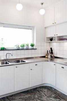 I det här huset från tidigt 50-tal har Byggfabriken byggt ett nytt kök i funkisstil. Traditionell funkis med en rad rundare skåp under överskåpen, specerifack i glas och knoppar typiska för köket. Rostfri diskbaän med infälld häll och vask sträcker sig över hela köket.