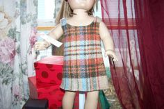 Jumper dress for 18 inch doll in woolen plaid with white cotton inner bodice lining. Fall colors of Beige, Brown, Blue, Green, Orange, and Red make up this adorable plaid Jumper. The back is secured from the neck to waist with tan hook & loop tape. Can be worn with or without a shirt or leggings beneath to change up the look.  Hand Made in our Smoke Free home with TLC by TLC, for your childs 18 inch dolls such as; American Girl, Springfield Doll, Journey Girls, Harmony Club, Madame Alexa...