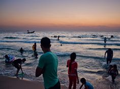 Gazans swim in the Mediterranean Sea at sunset. An Israeli naval blockade to stop smuggling of arms and other goods into the Gaza Strip—the heart of Palestinian resistance—also restricts Gazans to within three nautical miles of shore. But the sea is one place where they have an open horizon.