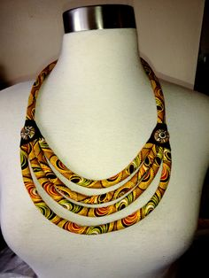 Authentic African Fabric necklace has lapped leather triangles with hand painted horn button embellishments.  Necklace is lightweight with cords