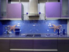 The kitchen is dominated by purple hues, with blue has the wallpaper.  The area gives a feeling of mystery with the purple, while also adding a tough of nature by the ocean characteristics on the blue wallpaper.