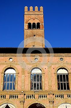 Photo made at the palace of King Enzo of Sardinia that is located in the city of Bologna in Emilia Romagna (Italy). In the image you see the wall, illuminated by the sun of a winter day, looking at the Basilica of San Petronio. On the wall you see the slender tower in the sky is a clear blue.