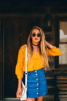Camisa amarela fica incrível com saia jeans de botões.