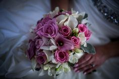 A bride holds her whimsical white, purple, and pink bouquet.