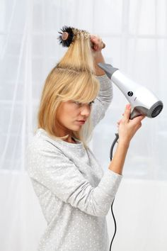 How to blow dry medium hair: Unclip the top section and dry the whole chunk at once: Pull it straight up and point the dryer up too, which will help lock in the lift.