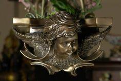 Przepiękna i niespotykana półka z głową anioła w stylu barokowym. Doskonałe w każdym szczególe współczesne wykonanie inspirowane XVIII-wiecznym wzorem. Niezwykle dekoracyjna, świetnie się prezentuje w każdym wnętrzu.  Tego rodzaju dekoracje ścienne dodają uroku, oraz specyficznego stylu każdej aranżacji.