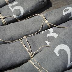 Linge de table : Sets de table 100% lin, numérotés de 1 à 6 et présentés dans un joli sac siglé Bed and Philosophy. Existera en Taupe, Orage et Charbon. Serviett...