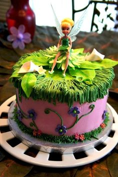 This is a fairy cake for a fairy themed birthday party for a 5 year old girl. It is filled and covered in SMBC, with American buttercream piping and MMF flowers/leaves. The inside is pink and purple!