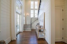 Stunning beach house foyer boasts white French glass paneled doors positioned beneath transom windows and covered with long white curtains facing a tiered console table topped with a gray abstract art piece leaning against a white shiplap wall.