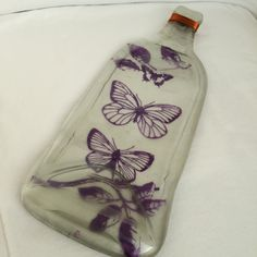 Purple Butterflies Painted on Flat Wine Bottle Tray. This melted glass tray made from a real bottle would make the perfect gift for any occasion such as birthday, housewarming, Mother's Day, bridesmaid gift, Christmas, wedding, or anniversary gift. The artwork is painted on the back in permanent paint. Comes with one cheese spreader & a hook on the back. Hand wash using mild soap. Tray can be used as a: -Cheese/Appetizer Platter (comes with one cheese spreader), Spoon Rest, Jewelry Tray...